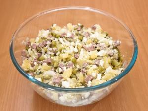 Соединяем все подготовленные ингредиенты из картошки, мяса, лука, горошка (жидкость сливаем), яиц, огурцов, по вкусу добавим соль, перемешиваем.