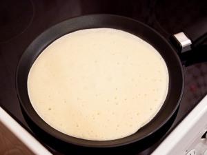 Предварительно разогреваем сковородку. Растительным маслом смазываем дно. Заливаем в сковородку готовое тесто, распределяя по всей сковороде. Чтобы тесто распределилось, немного покрутите сковородку. Когда наш блин снизу подрумянится, переворачиваем.