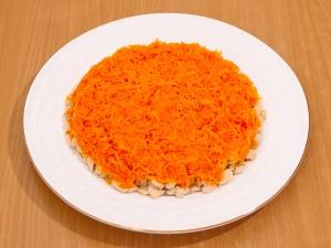 Следующим слоем идет морковь. Ее мы выкладываем на слой из куриного филе. Добавляем майонез, смазываем.