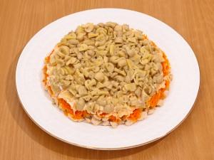 Третий слой будет из грибов. Выкладываем их на морковный слой и смазываем майонезом.