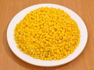 Шестым слоем, выкладываем кукурузу. Теперь берем чипсы и втыкаем их вокруг салата.
