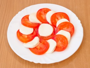 Нам понадобится тарелка. Выкладываем на нее по очередности (моцарелла, томаты).