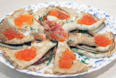 Сворачиваем блины вдвое и раскладываем в тарелку. Выкладываем верх кусочками рыбки и посыпаем мелко пошинкованным укропчиком.
