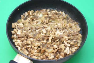 Далее берем предварительно разогретую сковородку. Добавляем примерно 2 столовых ложки раст/масла. Закладываем мелко по шинкованный лук с грибами и обжариваем около 2 минут.Снимаем, даем время остыть.
