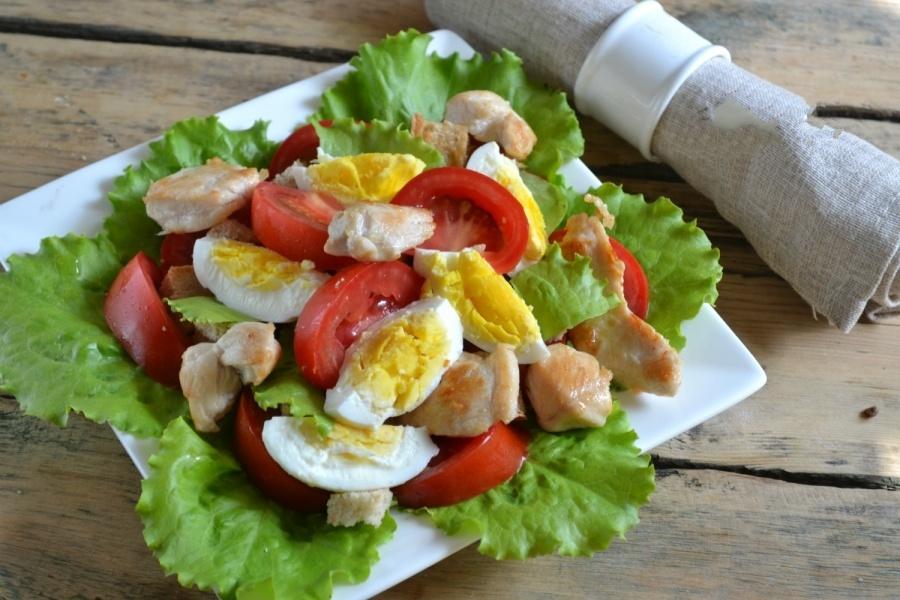 Выкладываем наш салатик. Берем салатник, или другое блюдо и на дно раскладываем, хорошо помытые листики салата.На верх уложите помидоры, сухари, нарезанные дольками яйца и куриное мясо.