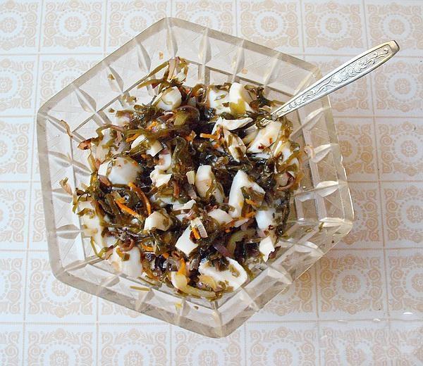 Тушеный перчик с лучком, порезанные кальмары и капусту (морскую), мы закладываем в блюдо для салата, или глубокую тарелку. Добавляем оливковое масло, по вкусу соль, все перемешать. Раскладываем в салатнике листья салата, и выложить крабовый салат.