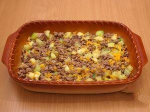 Берем формочку для выпечки и смажем растительным маслом. Кабачки с фаршем выложить в форму и разровнять.