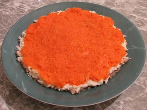 Следующим слоем выкладываем (протертую морковь). Выложили на белки, добавили немного майонеза, размазали по поверхности.