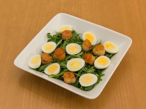 На тарелки с рукколой, выложить ингредиенты, гребешков, перепелиных яиц.