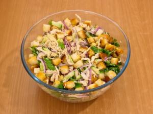 Закладываем приготовленные ингредиенты из огурчиков, лука, филейной части, сыра, заправки и сухарей.