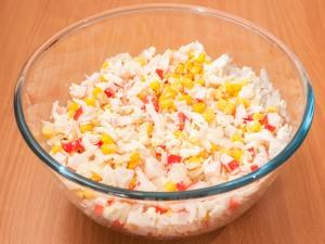 Из кукурузы сливаем воду. Соединяем ее с крабовыми палочками, луком и яйцами. Добавляем немножко соли.