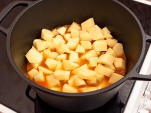 Запускаем картошку в кастрюлю с мясом и овощами.