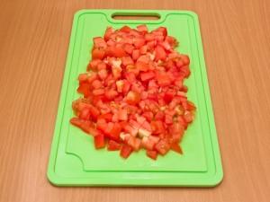На кубики порезать томаты.