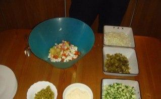 Чистим картошку с морковью, режем на кубики. Подобным образом нарезаются сосиски с яйцом. Соединяем резаные продукты, размешиваем, положить зеленого горошка. Заложить майонез, присолить, размешать.